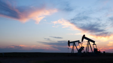 Two pump jack silhouettes at dusk on the prairie